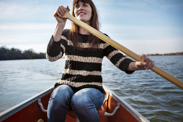 Smiling woman rowing boat on lake against sky during winter