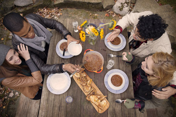 High angle view of friends having food at wooden table outdoors
