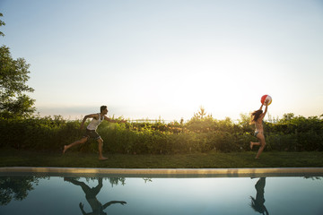 Woman with ball running at poolside while man running behind