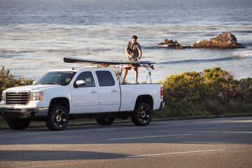 Man tying surfboard on pick-up truck parked at roadside against sea