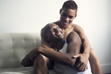Gay couple embracing while sitting at home