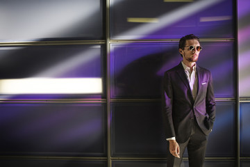 Purple lights falling on businessman standing against glass wall
