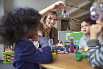 Smiling teacher showing solution to children while doing scientific experiment in preschool