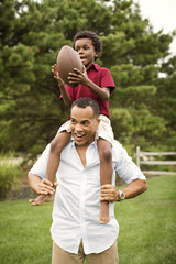 Boy sitting on his father's shoulders while holding rugby ball