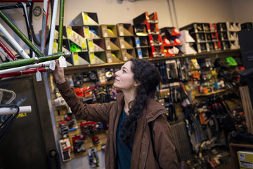 Woman looking at bicycle while standing in bicycle shop