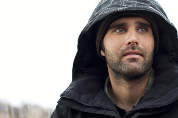 Thoughtful man wearing hooded jacket against clear sky during winter