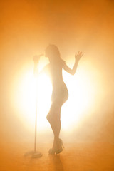 Silhouette of woman singing while standing on stage
