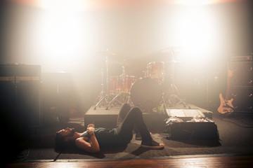 Side view of man lying on floor in rock music studio