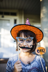 Portrait of smiling girl holding props during Halloween party