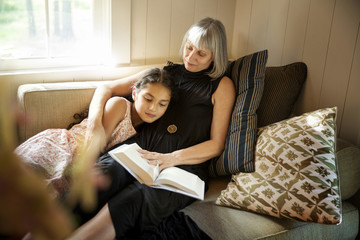 Grandmother reading book to granddaughter while resting on couch at home