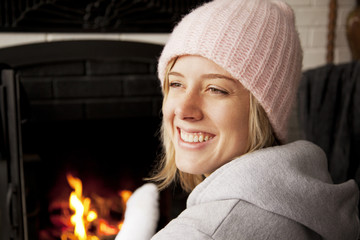 Smiling woman looking away while sitting by fireplace at home