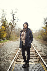 Thoughtful woman standing on railroad track against clear sky