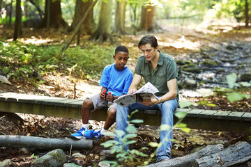 Teacher showing book to student while sitting on footbridge in forest