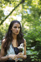 Thoughtful woman holding flowers while standing in forest