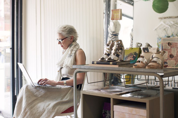 Senior woman using laptop while sitting on chair in shop