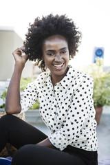 Portrait of happy woman sitting on building terrace