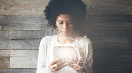 Futuristic technology and communication concept. Smiling pretty black girl with Afro hairstyle using digital tablet, checking email or typing a message. Visual effects. Worldwide connection interface