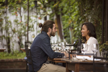 Side view of happy couple talking while sitting at sidewalk cafe