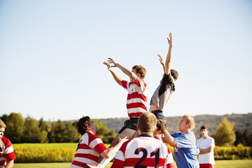 Sportsmen lifting rugby players with arms raised against clear sky