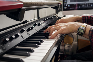 Cropped image of man playing piano at home