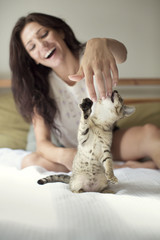 Happy woman playing with cat at home