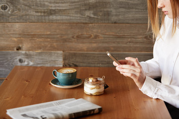 People, leisure and technology concept: young woman photographing sweet dessert on mobile phone, hipster girl taking photo of her morning breakfast using cell phone camera while sitting in cafe