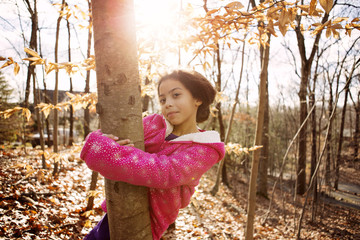 Portrait of girl embracing tree trunk during autumn