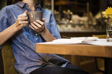 Midsection of woman holding coffee mug sitting at table in cafe