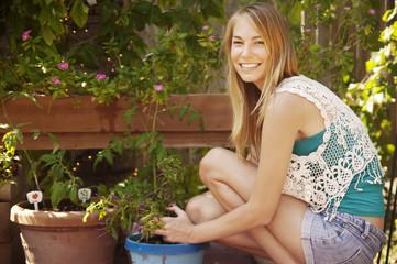 Portrait of woman planting in yard