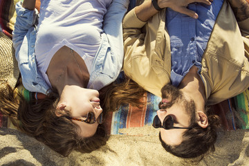 High angle view of couple relaxing on sand at beach