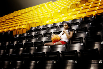 Woman with basketball sitting on seat in stadium