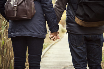 Midsection of couple holding hands while walking on boardwalk during winter