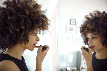 Side view of woman applying lipstick while looking at mirror