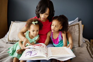 Woman with her daughters looking at drawing book