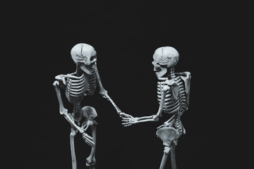Halloween is skeletons holding hands on black background