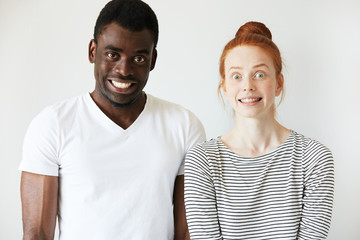 A couple grinning and making scary faces with false smiles and wide eyes. African man staring at camera and red-head Caucasian girl is freezed in stupefaction. Strange and crippy mimics, fun concept.