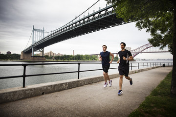 Friends running on promenade against Triborough bridge