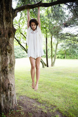 Full length of woman hanging on tree branch