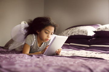 Girl with fairy wings using digital tablet