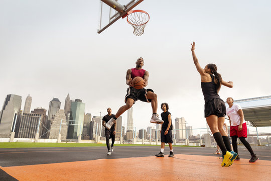 Group of friends playing basketball at  basketball court