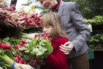 Woman looking at granddaughter smelling radish in market