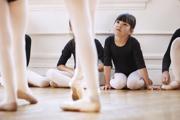 Cute girl looking at ballerinas dancing in studio
