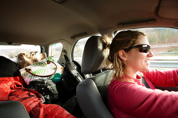 Smiling woman traveling with heap of bags in car on sunny day