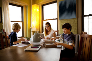 Mother sitting with sons doing homework at table