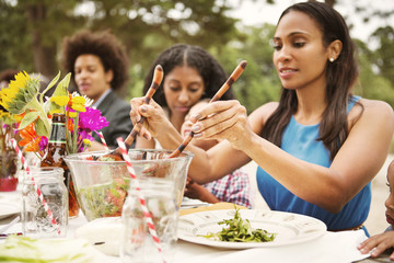Family enjoying meal while sitting at table in backyard