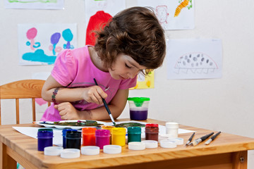 Little girl is drawing with paints and paintbrush
