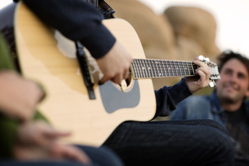 Midsection of man playing guitar while sitting with friend