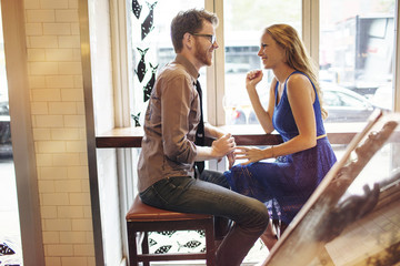 Happy couple talking while sitting in restaurant