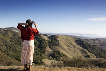 Rear view of woman standing on mountain and looking at view