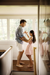 Father and daughter dancing in corridor by window at home